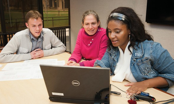 Randy Boley, left, a junior in psychology and pre-occupational therapy, and Precious Marie Walker, right, a senior in psychology and pre-med, work with Roberta Paikoff Holzmueller, center, associate professor of psychology.