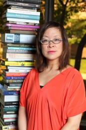 Lisa Lee stands next to a tower of books