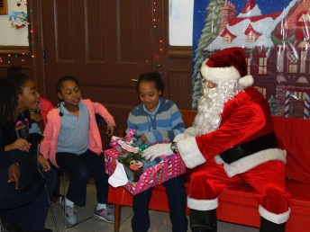 Officer Santa Braulio DeAnda hands out gifts at the UIC Police Station Friday.