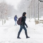 Girl walks through the snow on campus