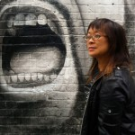 Lisa Lee in front of a graffiti face