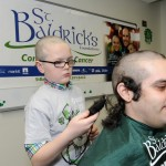 Boy shaving Alberto Locante's head for St. Baldrick's.