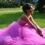 girl sitting in the grass in her prom dress
