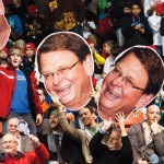 Fans in the crowd hold giant photos of Jerry Bauman's face
