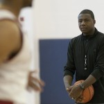 Howard Moore holds a basketball while watching his team practice