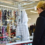 Girl looks at thrift store jewelry selection