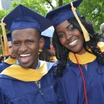 Two students pose with smiles after graduating