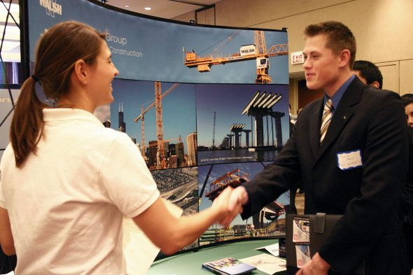 An engineering student networks at job fair