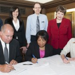 Signing the contract (L-R back row): members of the campus negotiating team, Michael Ginsburg, associate vice chancellor for student affairs, Tonia Nikopoulos, assistant dean, College of Liberal Arts and Sciences, Steven Kregon, executive assistant dean, Graduate College, Marilyn LaBlaiks, assistant director of labor and employee relations, and Liz Sauer, GEO; (front row) Tom Riley, director of labor and employee relations, Chancellor Paula Allen-Meares and Marissa Baker, GEO co-president.