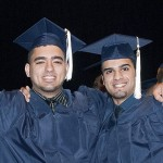 Two graduates hold up their diplomas