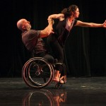 Performer in a wheelchair holds up a woman