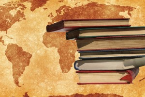 Stack of books in front of a world map