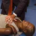 Man practices CPR on a dummy;