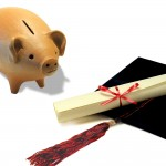 Piggy bank next to a graduation cap and diploma