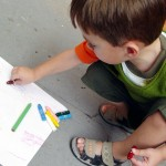 Young boy drawing with crayons