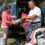 Girl and her father unpack her belongings from their car