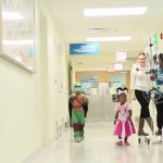 Children walk down hospital hallway in Halloween costumes