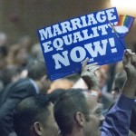 "Person holding a ""marriage equality now"" sign in the crowd"