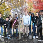 Volunteers pose with shovels around newly-planted tree