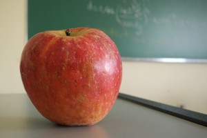 An apple on a desk with a chalkboard in the background