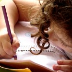 young girl drawing in a workbook
