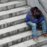 Homeless youth sitting on steps