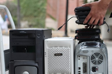 Person stacking electronics for recycling