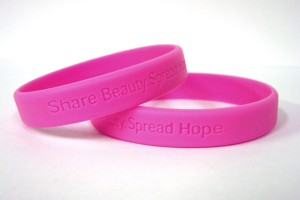 "Breast cancer awareness bracelets that read ""Share Beauty. Spread Hope."""