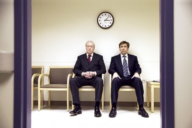Michael Caine and Nicholas Cage sitting in a waiting room