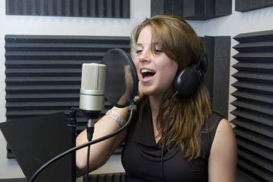 young woman singing at a recording studio