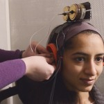 Researcher affixing a device to a participant's ear