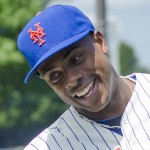 Curtis Granderson high-fives a participant at his baseball camp