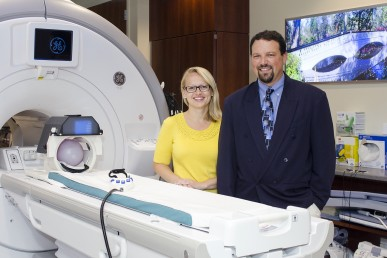Rachel Jacobs and Scott Langenecker with an MRI machine