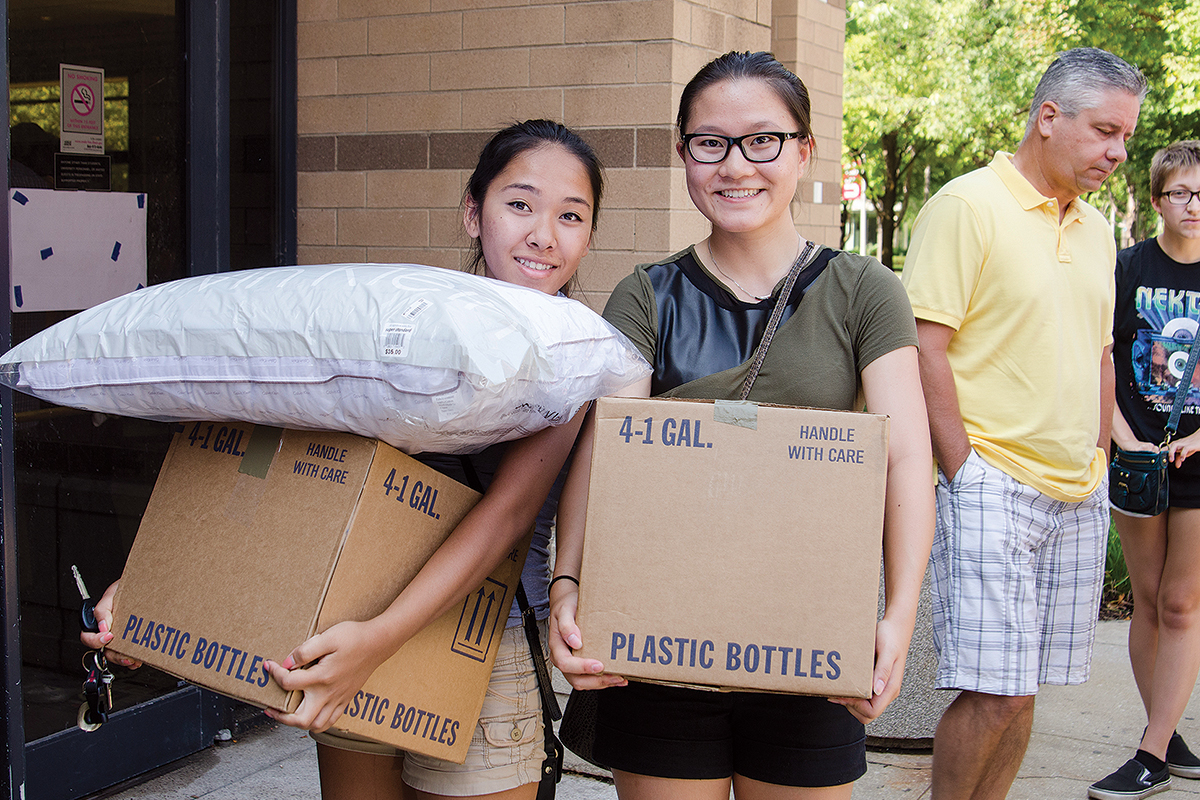Ottissa Lau and friend Miranda Souvanh carry boxes into the residence hall