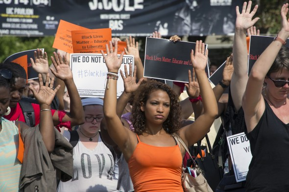 Supporters of Michael Brown raise their hands and hold signs of protest against police brutality
