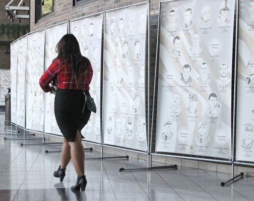 Woman walks past Portraits of a Soldier exhibit