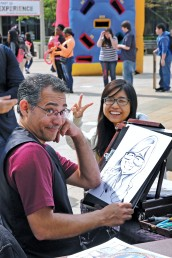 Caricature artist and his subject pose for a photo