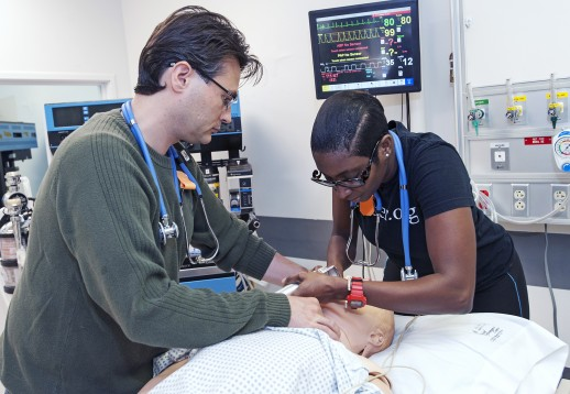 Students work together to insert a breathing tube in a dummy patient