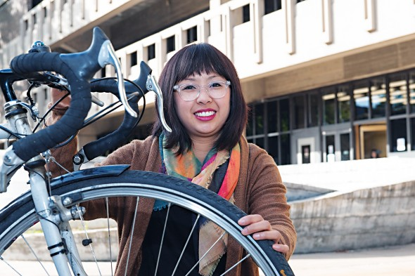 Annie Pho and her bicycle in front of the Daley Library