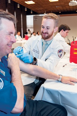 Conrad Pomykala recieves his flu shot from pharmacy student Jacob Sicinski