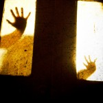 Silhouette of hands through a window