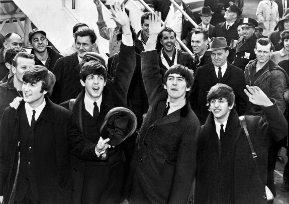 Beatles wave to fans after arriving at Kennedy Airport, Feb. 7, 1964