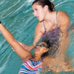 Young woman learning to swim with instructor
