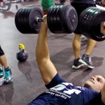 student lifting weights at the gym