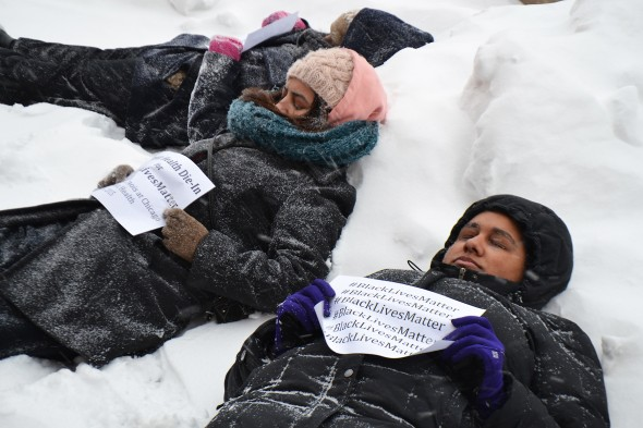 students laying in the snow