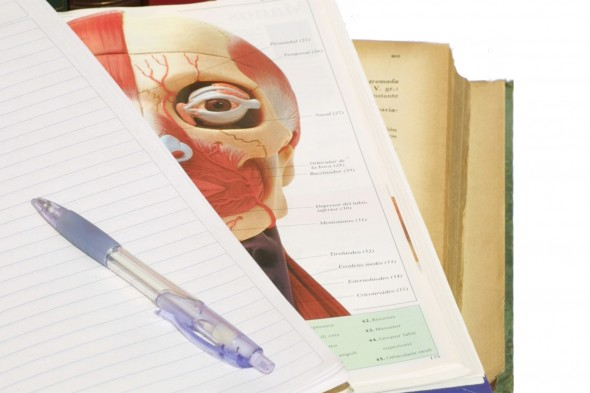 notebook and pen on top of anatomy textbook