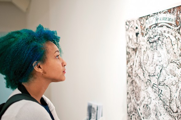 "woman looking at a painting in ""Here, There, Everywhere"""