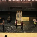 """Rehearsing students dance before a """"stairway to heaven"""" under construction."""