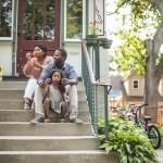 Family sits on front steps