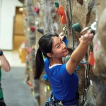 young woman climbing a rock wall, man in the background belaying